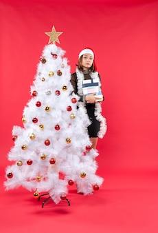Belle jeune femme avec chapeau de père noël et debout derrière l'arbre de noël décoré tenant des cadeaux et à la recherche de quelque chose