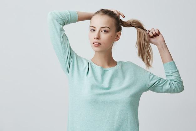 Belle jeune femme avec de charmants yeux noirs et des cheveux blonds en queue de cheval portant un pull bleu clair