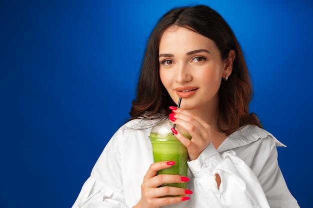 Belle jeune femme en chemise blanche buvant un smoothie vert sur fond bleu