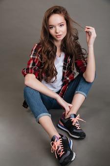 Belle jeune femme en chemise à carreaux et jeand assis