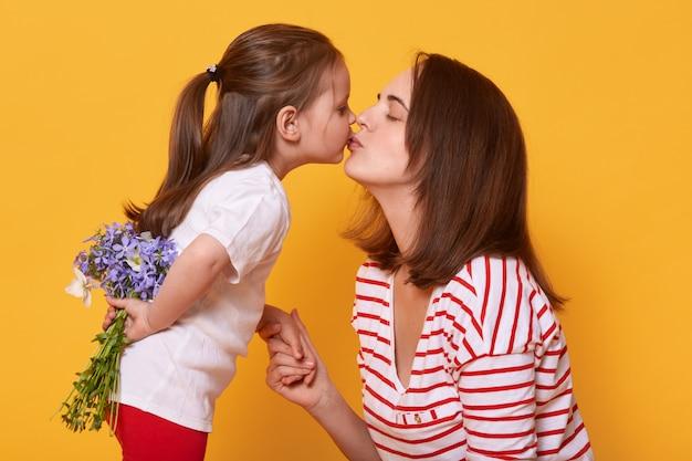 Belle jeune femme en chemise rayée tient la main de sa fille et l'embrasse.