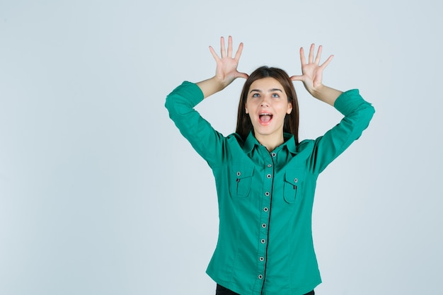 Belle jeune femme en chemise verte tenant les mains sur la tête comme des oreilles et à la drôle, vue de face.