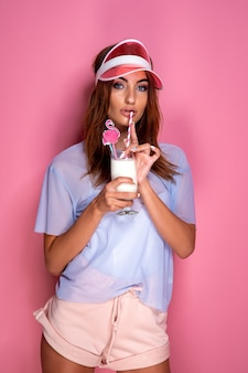 Belle jeune femme en chemise et visière en plastique tenant un verre de boisson délicieuse en se tenant debout sur le mur rose
