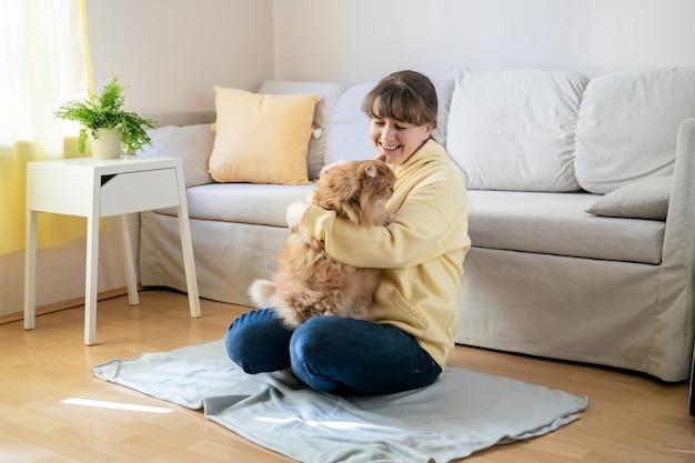 Belle jeune femme en chemisier jaune vif avec joli chat gingembre à la maison. zone de confort à la maison.
