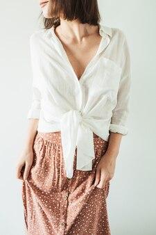 Belle jeune femme en chemisier, jupe sur blanc