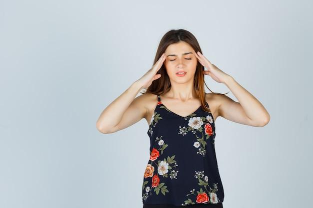 Belle jeune femme en chemisier souffrant de forts maux de tête et à la fatigue