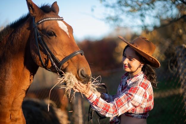Belle jeune femme et cheval d'alimentation pendant l'automne