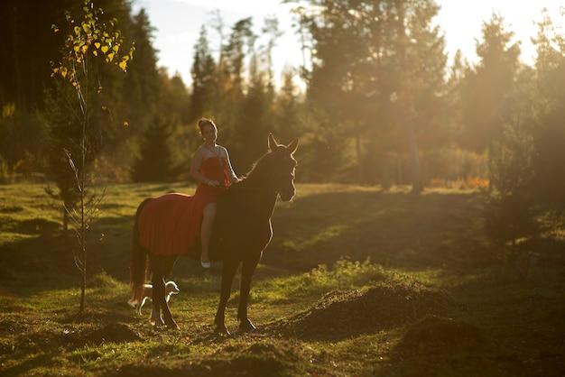 Belle jeune femme et cheval brun pendant l'automne