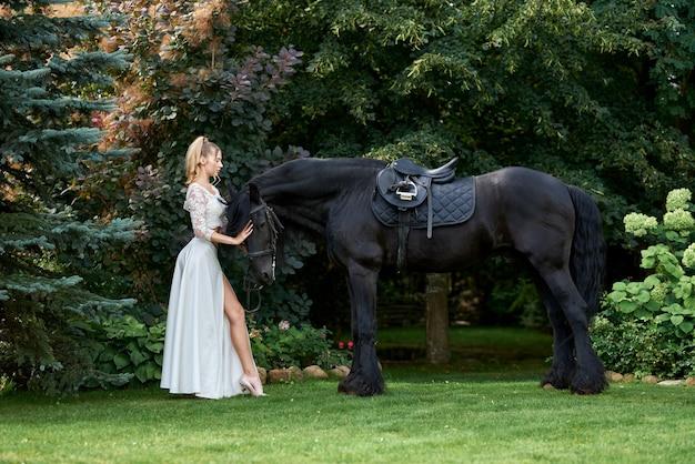 Belle jeune femme avec un cheval noir