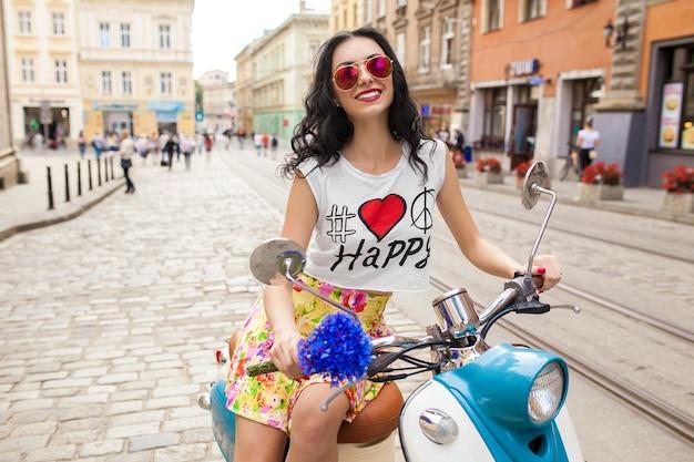 Belle jeune femme à cheval sur la rue de la ville de moto