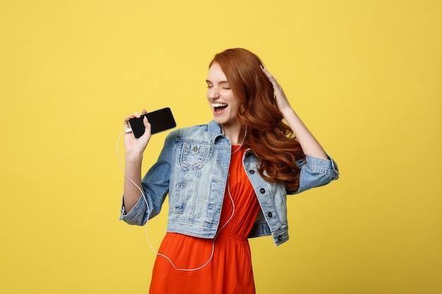 Belle jeune femme cheveux roux bouclés dans les écouteurs en écoutant de la musique et la danse.