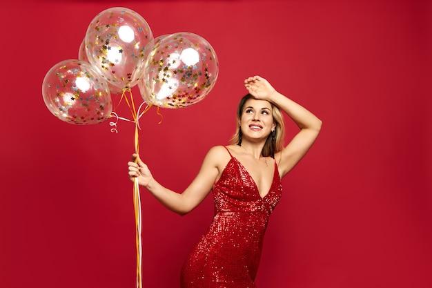 Belle jeune femme chic vêtue d'une robe rouge à col bas posant et tenant des ballons