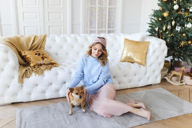 Belle jeune femme avec un chien sur le fond d'un arbre de noël
