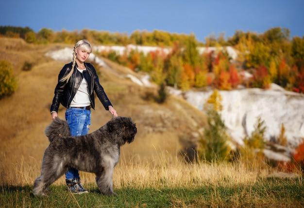 Belle jeune femme avec un chien de race flandre bouvier