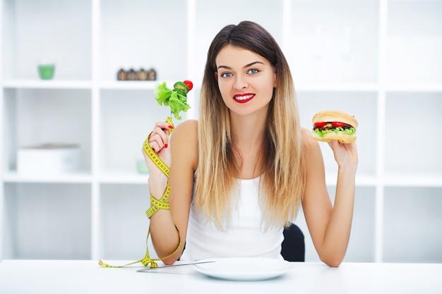 Belle jeune femme choisissant entre la nourriture saine et la malbouffe