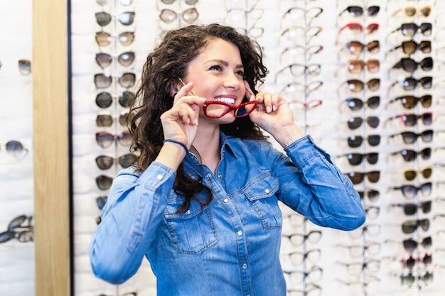 Belle jeune femme choisissant une monture de lunettes en magasin d'optique.