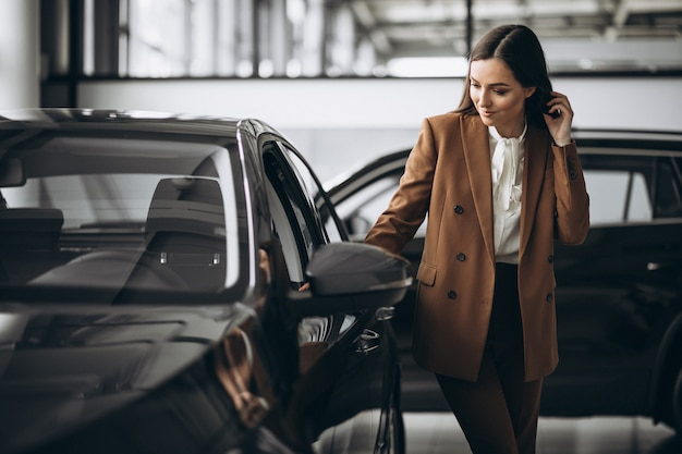 Belle jeune femme choisissant la voiture dans une salle d'exposition de voiture