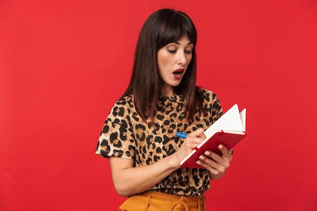 Belle jeune femme choquée vêtue d'une chemise imprimée d'animaux posant isolée sur un mur rouge, écrivant des notes dans un cahier.