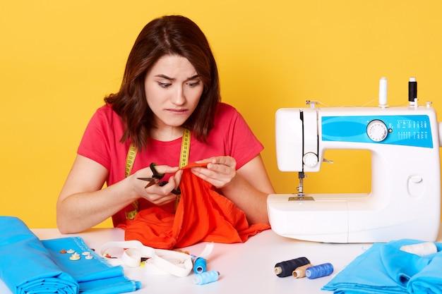Belle jeune femme ciblée créatrice de mode coupe un morceau de tissu rouge pour une nouvelle tenue