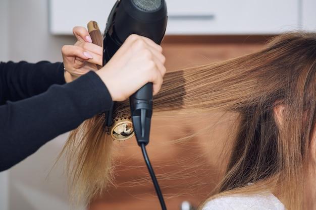 Belle jeune femme cliente faisant du coiffage chez un coiffeur professionnel dans un gros plan de salon de beauté