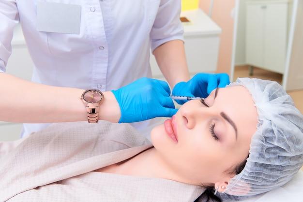 Belle jeune femme en clinique de cosmétologie esthétique.