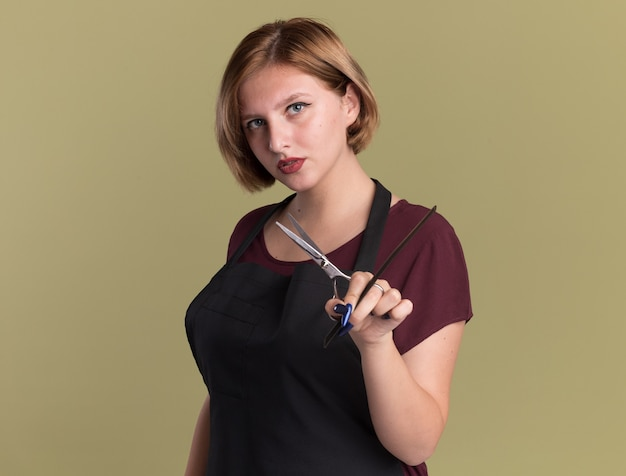 Belle jeune femme coiffeur en tablier avec des ciseaux et un peigne à cheveux regardant à l'avant avec un visage sérieux debout sur un mur vert