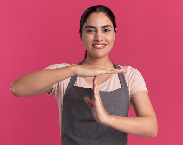 Belle jeune femme coiffeur en tablier à la recherche à l'avant souriant faisant le temps de geste debout sur le mur rose