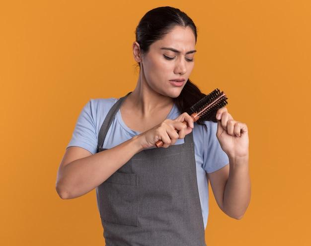 Belle jeune femme coiffeur en tablier se brosser la queue avec un visage sérieux debout sur un mur orange