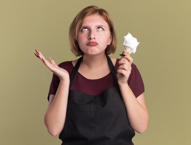 Belle jeune femme coiffeur en tablier tenant un blaireau avec de la mousse à raser à l'ennui roulant les yeux debout sur le mur vert