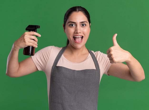 Belle jeune femme coiffeur en tablier tenant le flacon pulvérisateur à l'avant souriant joyeusement montrant les pouces vers le haut debout sur le mur vert