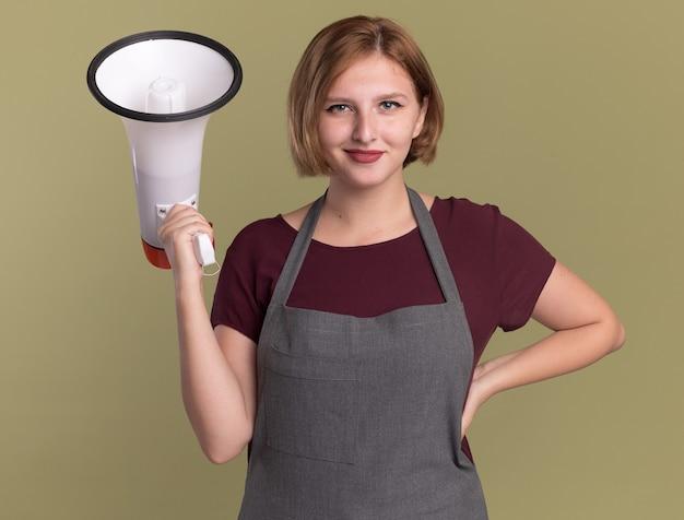 Belle jeune femme coiffeur en tablier tenant un mégaphone à l'avant souriant confiant debout sur mur vert