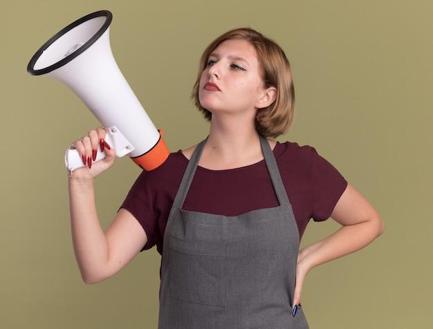 Belle jeune femme coiffeur en tablier tenant un mégaphone à côté avec un visage sérieux debout sur un mur vert