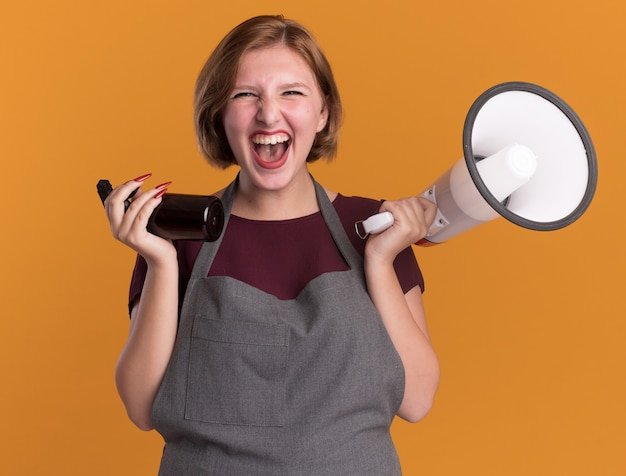 Belle jeune femme coiffeur en tablier tenant mégaphone et vaporisateur fou heureux et excité debout sur le mur orange