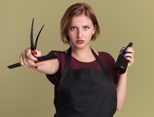 Belle jeune femme coiffeur en tablier tenant un peigne à cheveux et un vaporisateur à l'avant avec un visage sérieux debout sur un mur vert