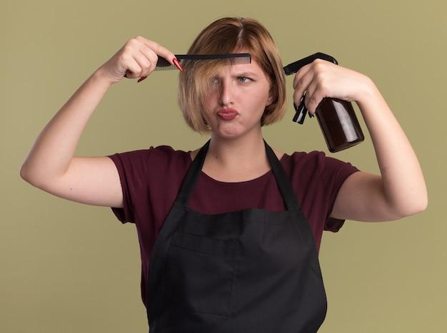Belle jeune femme coiffeur en tablier tenant une pince à cheveux vaporisateur et peigne à la confusion et mécontent debout sur le mur vert