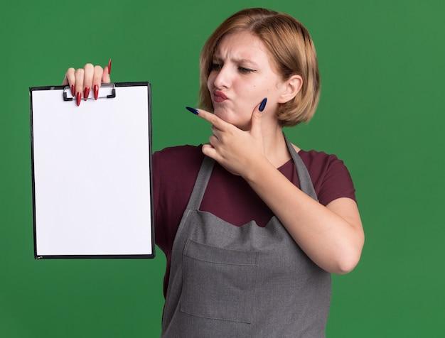 Belle jeune femme coiffeur en tablier tenant le presse-papiers avec des pages vierges en regardant la pensée confuse debout sur le mur vert