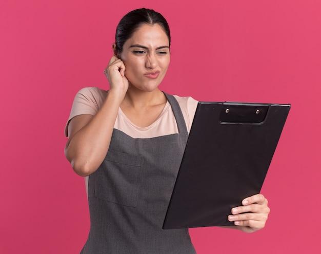 Belle jeune femme coiffeur en tablier tenant le presse-papiers en le regardant confus et mécontent debout sur le mur rose