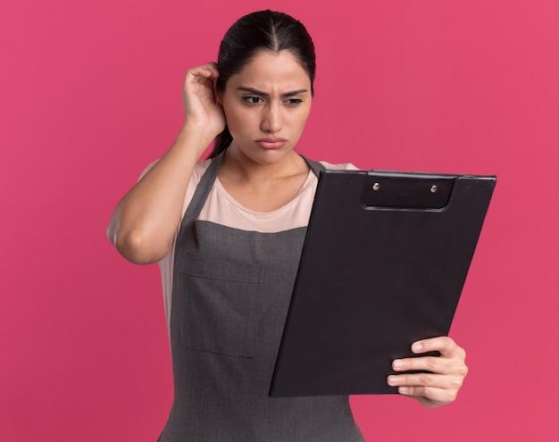 Belle jeune femme coiffeur en tablier tenant le presse-papiers en le regardant avec un visage sérieux debout sur un mur rose