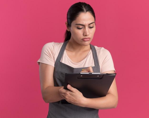Belle jeune femme coiffeur en tablier tenant le presse-papiers en le regardant avec un visage sérieux écrit quelque chose debout sur un mur rose
