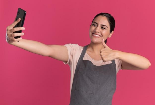 Belle jeune femme coiffeur en tablier tenant le smartphone en le regardant faire selfie montrant les pouces vers le haut souriant debout sur le mur rose