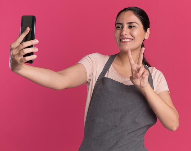 Belle jeune femme coiffeur en tablier tenant le smartphone en le regardant faire selfie souriant montrant v-sign debout sur le mur rose