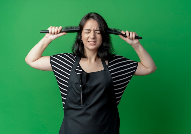 Belle jeune femme coiffeuse en tablier avec médaille d'or autour du cou tenant deux brosses à cheveux entendre ses tempes déçues sur le vert