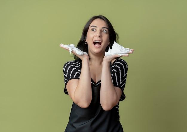 Belle jeune femme coiffeuse en tablier avec de la mousse à raser sur ses mains à la confusion debout sur un mur léger