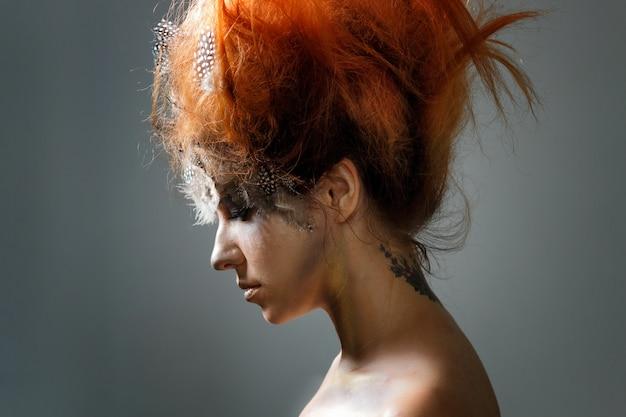 Belle jeune femme avec une coiffure avant-gardiste compliquée. tonifiant, photo d'art.
