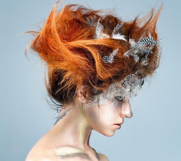 Belle jeune femme avec une coiffure avant-gardiste compliquée.