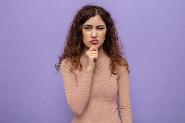 Belle jeune femme en col roulé beige avec la main sur son menton avec une expression pensive debout sur un mur violet