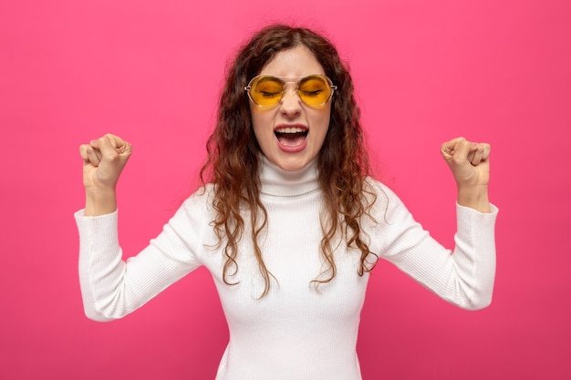 Belle jeune femme en col roulé blanc portant des lunettes jaunes levant les poings en criant avec une expression agacée debout sur rose