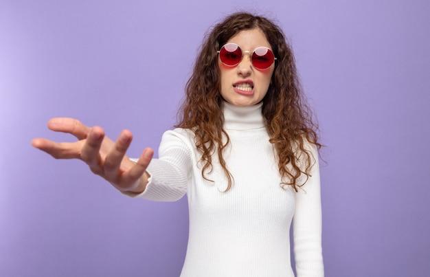 Belle jeune femme en col roulé blanc portant des lunettes rouges confus levant le bras dans l'indignation debout sur le violet
