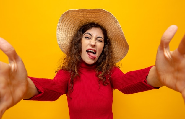 Belle jeune femme en col roulé rouge en chapeau d'été heureux et joyeux s'amusant à sortir la langue debout sur l'orange