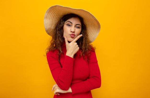 Belle jeune femme en col roulé rouge en chapeau d'été avec la main sur son menton avec une expression pensive debout sur un mur orange